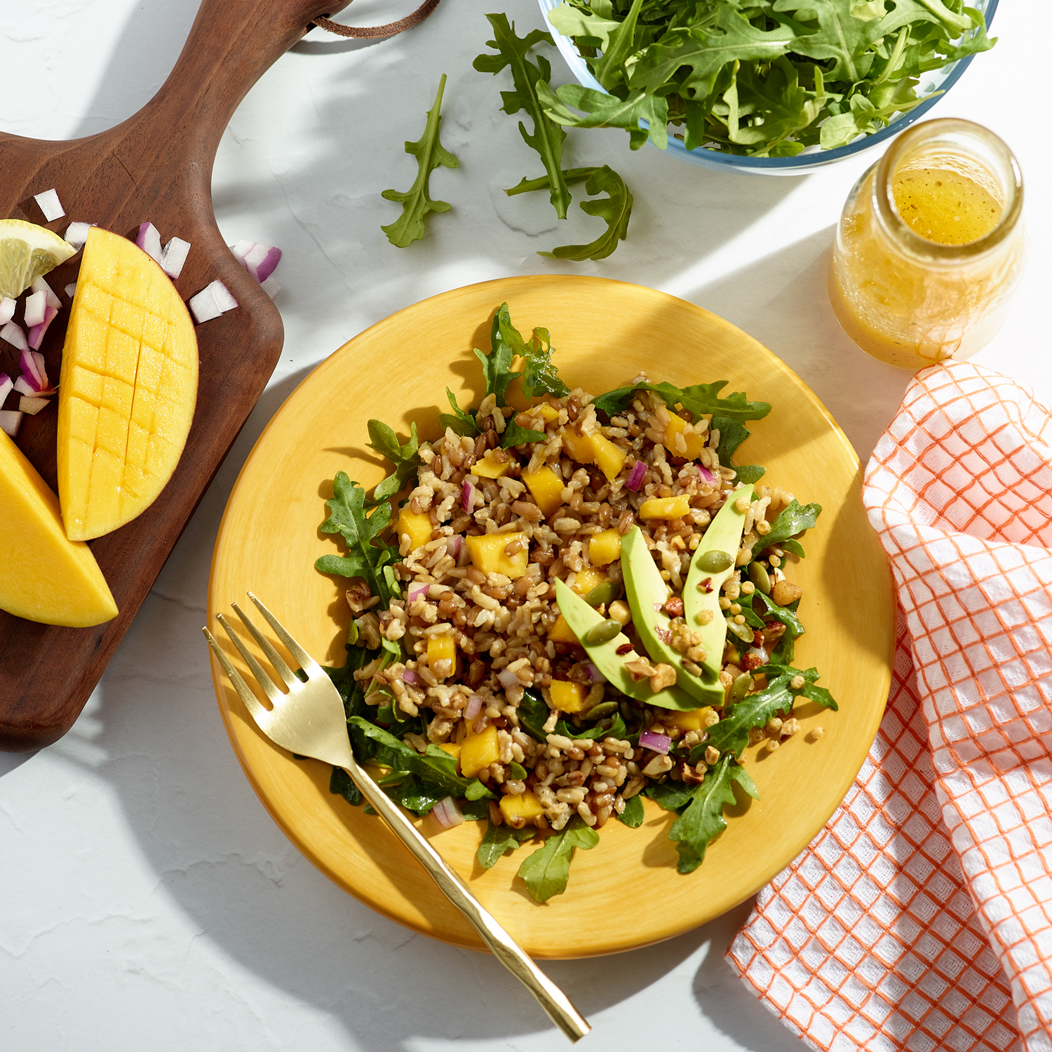 Overhead view of a yellow plate on a white background with an arugula salad with MWELL grains and avocados. A glass container of yellow vinagette dressing, cutting board with mango and onions and bowl of fresh arugula surrounds the plate. A white and orange pattered dish cloth is beside the plate.