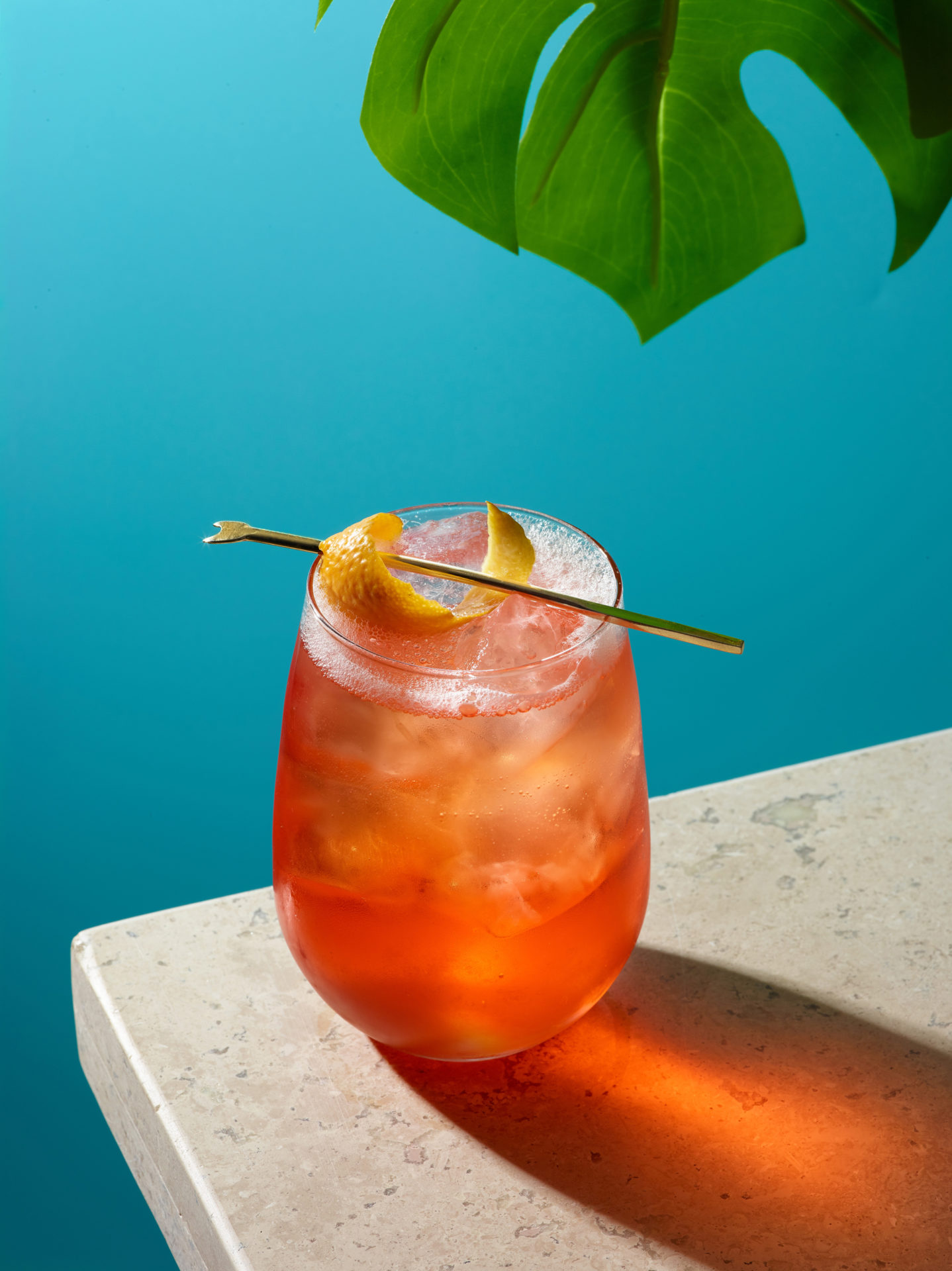 Aperol Spritz with orange peel garnish on a beige stone surface with a bright blue background. Served in a stemless wine glass over ice, the drink is a vibrant reddish orange color. A tropical leaf is hanging into the frame from the upper left side.